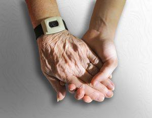 mano de anciana con dispositivo de salud. Telesalud ayuda a domicilio