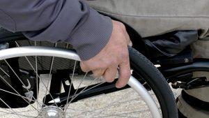 mano de un anciano sobre la rueda de una silla de ruedas. Actividades para ancianos con movilidad reducida