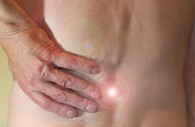 imagen mostrando una mano en la espalda por un dolor lumbar que puede ser tratado con fisioterapia en casa